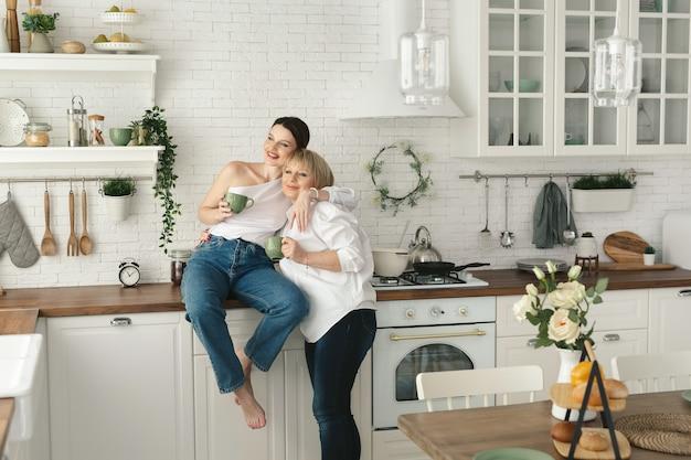 台所で幸せな高齢の母と娘、お茶を飲みながら会話を楽しむ。自宅で大人の娘を持つ老母 Premium写真