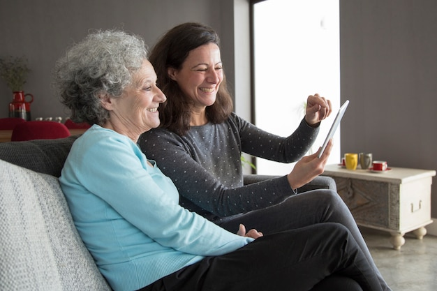 Happy elderly woman and her daughter browsing on tablet computer Free Photo