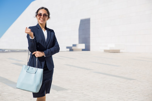 Happy elegant business lady heading to her office Free Photo