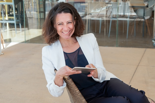 Happy elegant female tourist using tablet Free Photo