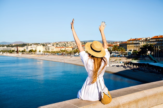 Happy elegant woman posing back, put her hand in the air and enjoying amazing view Free Photo