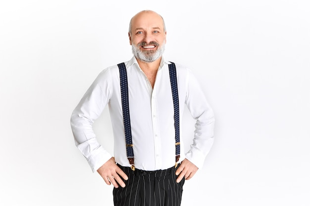 Happy emotional elderly man with gray beard and bald head rejoicing, holding hands on his waist, smiling cheerfully, posing against white background with copy space for your text Free Photo