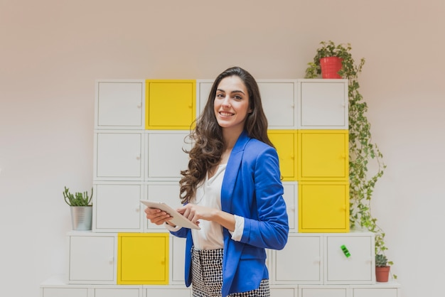Happy employee with tablet in the office Free Photo