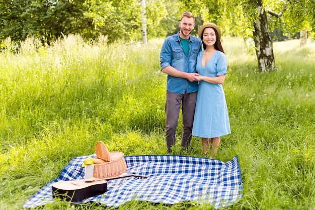 Happy enamored couple holding hands standing on sunny meadow Free Photo