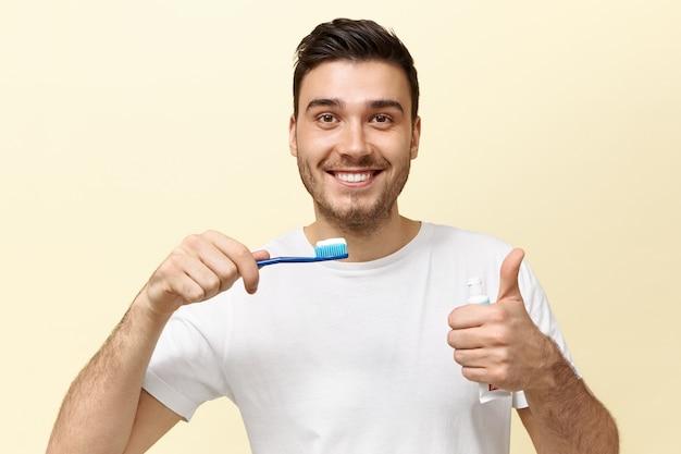 Felice giovane ragazzo europeo energico con stoppie tenendo lo spazzolino da denti con pasta sbiancante e mostrando il pollice in alto gesto di buon umore. Foto Gratuite