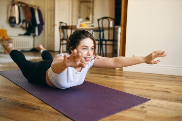 幸せなエネルギッシュな若い女性は、顔を下にして横になり、足を上げ、腕を伸ばし、脊椎の強さのために後屈します。 無料写真