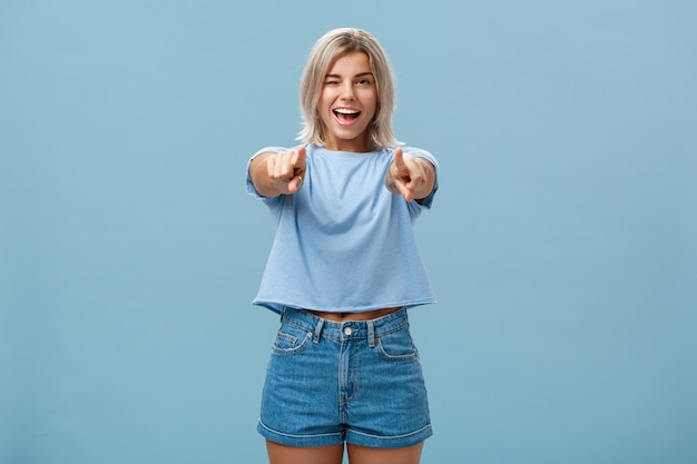 Happy enthusiastic stylish blonde female picking or making hint smiling joyfully and winking from amazement and happiness posing over blue wall Premium Photo
