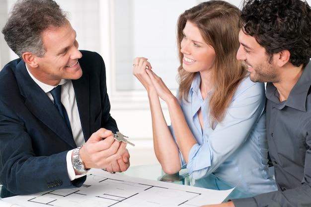 若いカップルに新しい家の鍵を示す幸せな不動産エージェント Premium写真