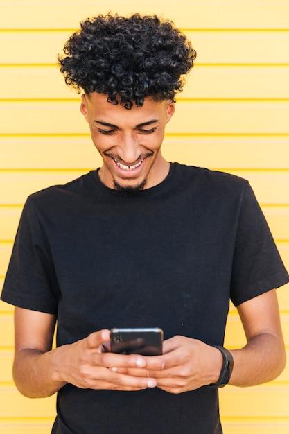 Happy ethnic male browsing phone Free Photo