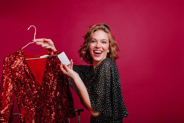 Счастливая европейская модель нашла дешевое красное блестящее платье для вечеринки Бесплатные Фотографии
