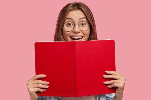Felice studentessa europea con gli occhiali, ha un'espressione positiva, tiene il libro rosso, si rallegra con successo superato l'esame all'università, isolato su un muro rosa. persone, apprendimento, lettura Foto Gratuite