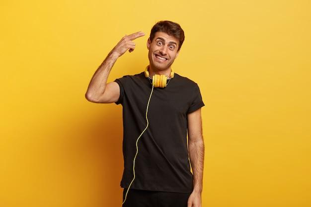 幸せなヨーロッパ人は寺院で撃ち、カジュアルな黒いtシャツを着て、首にヘッドフォンを着て、頭を傾けます 無料写真