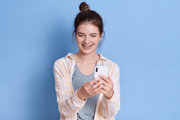幸せなヨーロッパの女性は、スマートフォンで面白いビデオを見て、電子機器でワイヤレスインターネットを使用し、優しく微笑んで、カジュアルな服を着ます。 無料写真