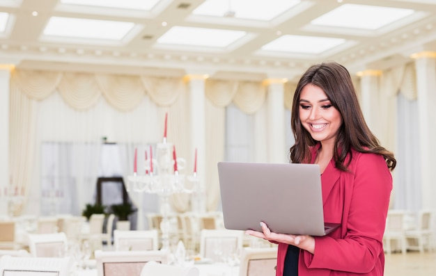 Happy event manager using laptop in banquet hall Free Photo