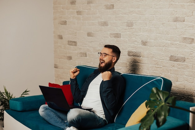 Premium Photo Happy Excited Bearded Man In Eyeglasses Sitting On Blue Sofa With Laptop At Home He Celebrate Online Victory