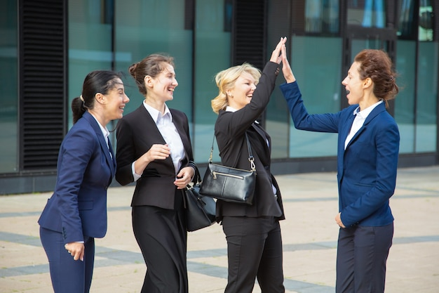 ハイファイブを与える幸せな興奮しているビジネスレディース。成功を祝う市で会議のスーツを着ているビジネスウーマン。チームの成功とチームワークの概念 無料写真