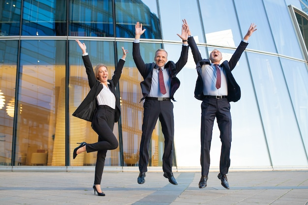 Happy excited business people celebrating success together, jumping and shouting. full length, front view. successful team and teamwork concept Free Photo