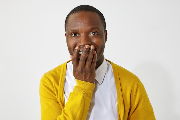 Felice eccitato maschio dalla pelle scura che copre la bocca con la mano, non posso credere a notizie positive sorprendenti. ritratto del ragazzo africano attraente emotivo che indossa abiti alla moda sorridendo eccitato Foto Gratuite