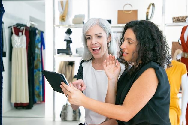 Счастливые взволнованные покупательницы сидят вместе и обсуждают одежду и покупки в магазине модной одежды. скопируйте пространство. потребительство или концепция покупок Бесплатные Фотографии