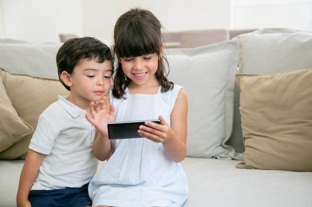 Счастливая взволнованная девочка и ее младший брат играют в онлайн-игру по телефону, сидя на диване в гостиной. Бесплатные Фотографии