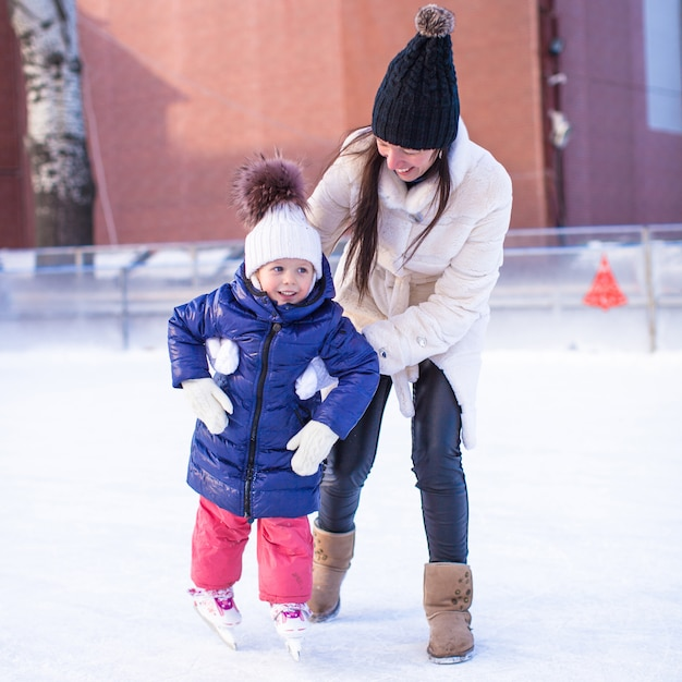 Happy excited little girl and her young mother learning ice-skating Premium Photo