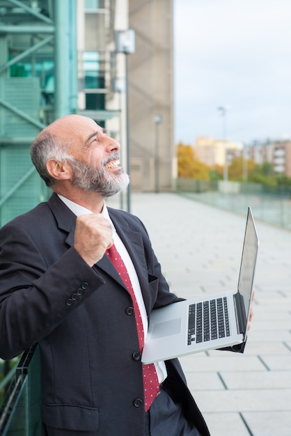 Happy excited mature business leader with laptop Free Photo