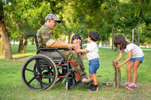 Felice mamma eccitata e papà militare disabile in sedia a rotelle che trascorrono il tempo libero con i bambini all'aperto, organizzando legna da ardere per il fuoco sull'erba. veterano disabili o concetto di famiglia all'aperto Foto Gratuite