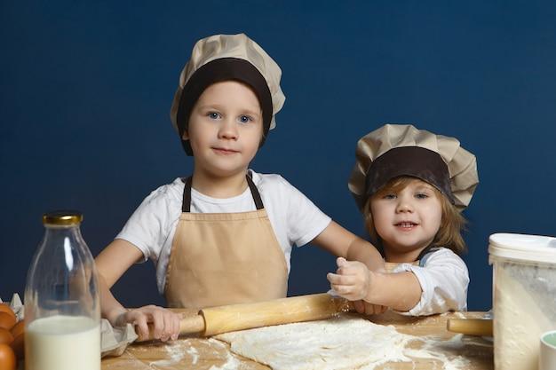 그의 여동생이 그를 돕는 동안 롤링 핀을 사용하여 반죽을 평평하게하는 행복 한 흥분된 모범생. 함께 피자를 만드는 두 귀여운 아이 형제 무료 사진