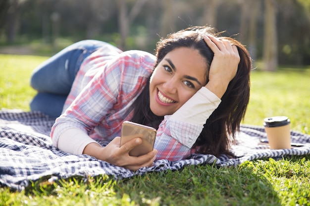 Happy excited student girl resting in park and sending messages Free Photo