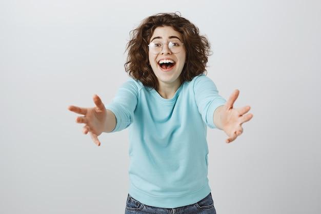 Счастливая взволнованная женщина, протягивая руки вперед, чтобы что-то подержать или взять Бесплатные Фотографии