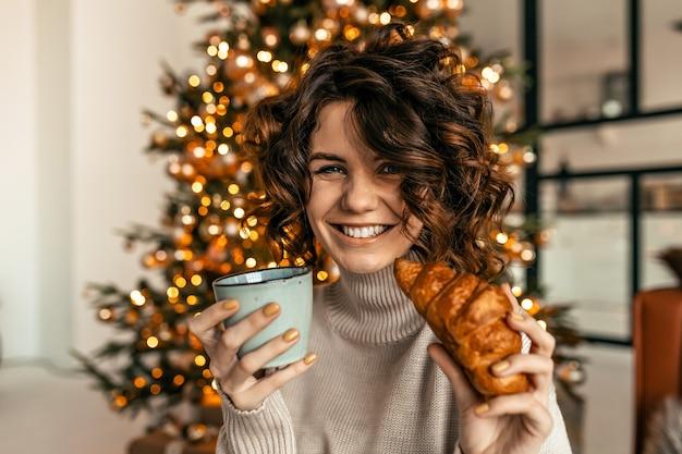 Счастливая возбужденная женщина с короткими вьющимися волосами позирует с круассаном и кофе рождественской елки Бесплатные Фотографии