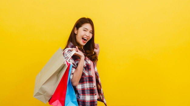 Happy excited young asian lady carrying shopping bags with hand raising up in casual clothing and looking at camera over yellow wall. facial expression, seasonal sale and consumerism concept. Free Photo