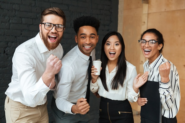 Happy excited young business colleagues make winner gesture. Free Photo