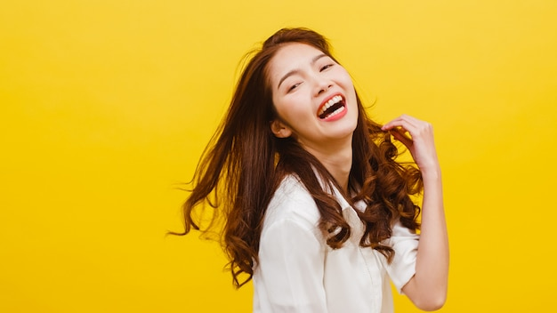 Happy excited young funny asian lady listening to music and dancing in casual clothing over yellow wall. human emotions, facial expression, studio portrait, lifestyle concept. Free Photo