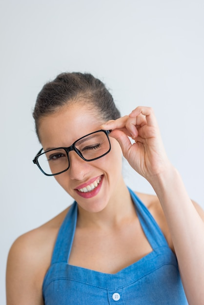 1f07d19754a Happy excited young woman adjusting eyeglasses and winking at camera. Free  Photo