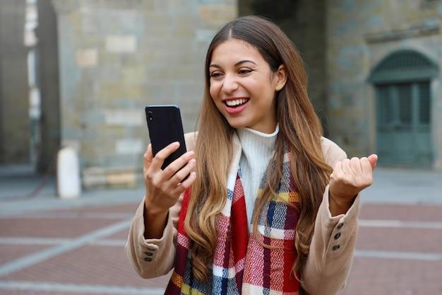 幸せな興奮した若い女性が携帯電話で良いニュースを見て笑って街の通り、冬時間 Premium写真