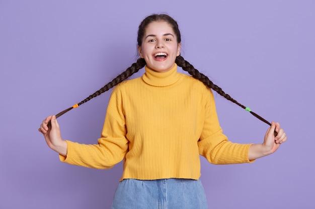 暗い長い髪の幸せな興奮している若い女性、おさげ髪を保持し、キューを脇に広げて 無料写真