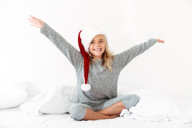 Счастливая возбужденная белокурая девушка в шляпе санты сидит на кровати с поднятыми руками, Бесплатные Фотографии