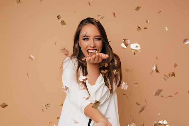 베이지 색 배경 위에 사진 촬영 중 색종이를 불고 흰색 재킷에 행복 종료 소녀 무료 사진