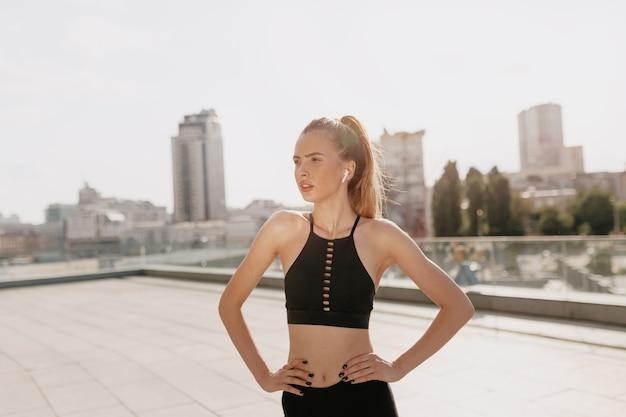 幸せな街で日当たりの良い夏の日に外でヘッドフォンでトレーニング意欲の高い女性を終了しました。健康的なアクティブなライフスタイルのヨーロッパの女性は屋外で運動します。 無料写真