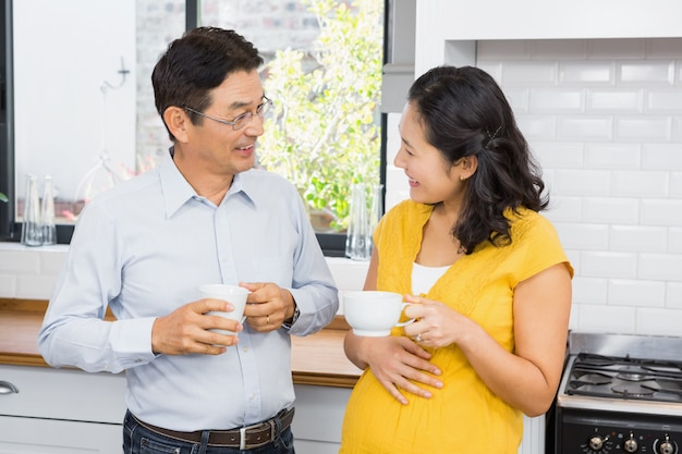 Happy expectant couple talking in the kitchen Premium Photo