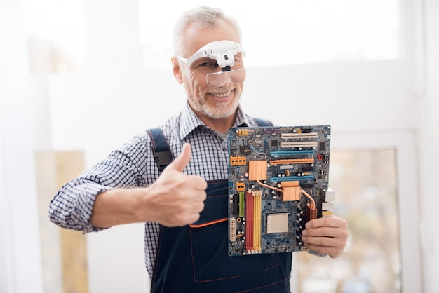 Happy experienced engineer is holding motherboard. Premium Photo