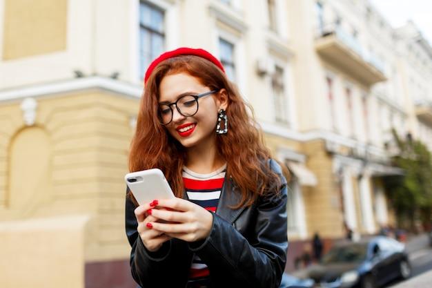スマートフォンを使用して通りでスタイリッシュな赤いベレー帽で幸せな素晴らしい生姜女 無料写真