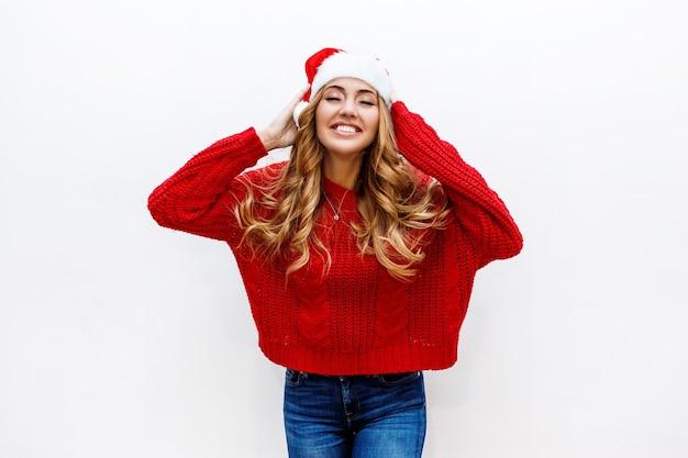 Volto felice. donna estatica in cappello e maglione rossi di travestimento del nuovo anno Foto Gratuite