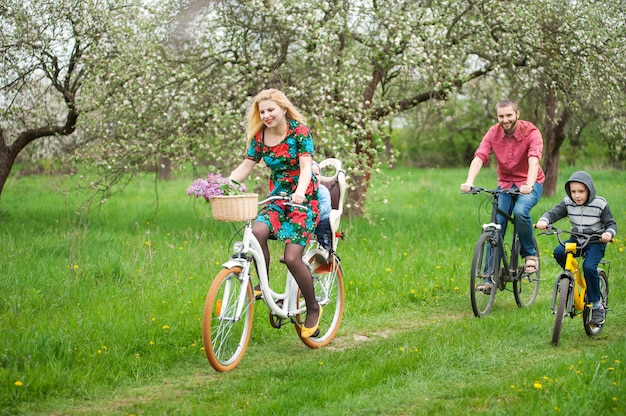 Happy family on a bicycles in the spring garden Premium Photo
