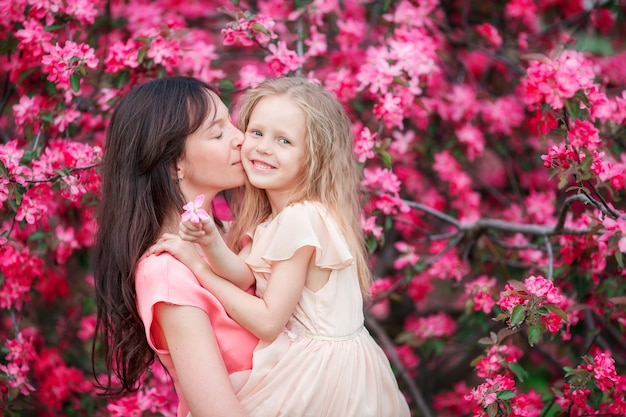 Happy family in blooming apple garden on beautiful spring day Premium Photo