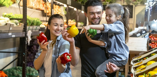Happy family buys vegetables. cheerful family of three choosing tomatoes in vegetable department of supermarket or market. Free Photo