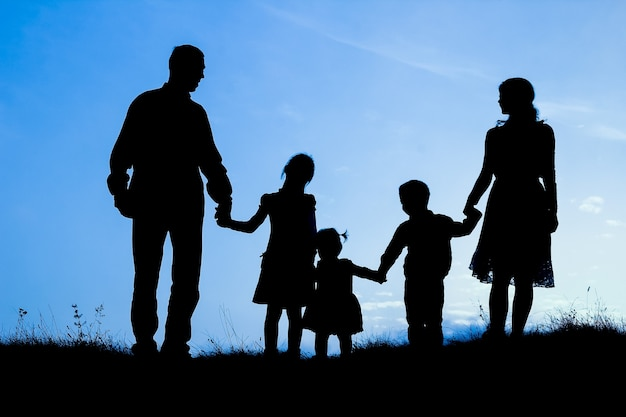 Happy family by the sea on nature silhouette Premium Photo