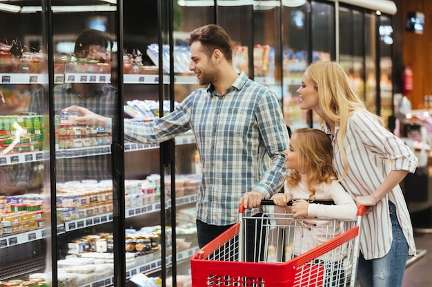 Happy family choosing groceries together Free Photo