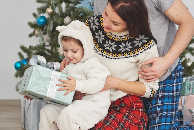 Happy family at christmas in morning opening gifts together near the fir tree. the concept of family happiness and well-being Premium Photo